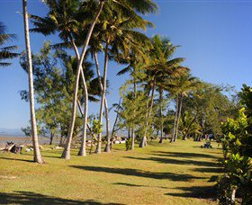 Conway Beach lined with grassy areas and shaded by trees